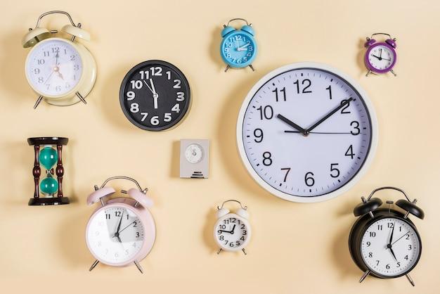 砂時計の種類が異なります。時計とベージュ色の背景上の目覚まし時計 無料写真