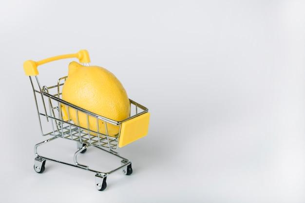 白い背景の上のショッピングカートに黄色いレモンのクローズアップ 無料写真