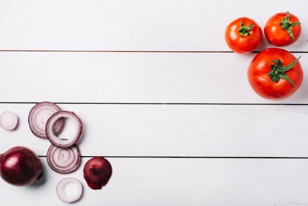 新鮮な玉ねぎとトマトの木製の背景の立面図 無料写真