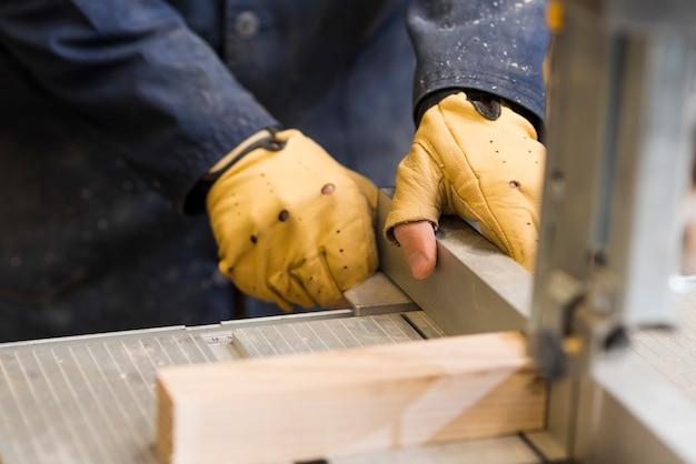 Конец-вверх рук плотника работая с деревянным блоком на верстаке Бесплатные Фотографии