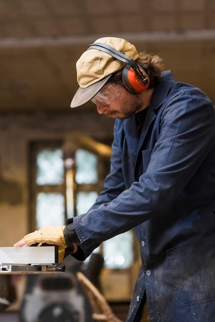 ワークショップで働く耳の防衛を着用している男性の大工の肖像 無料写真