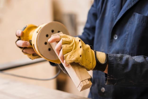 木製のブロックをサンダーでサンディングする男性の大工のクローズアップ 無料写真