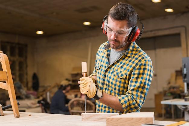 ワークショップで木製のブロックでチゼルのハンマーを打つ大工のクローズアップ 無料写真