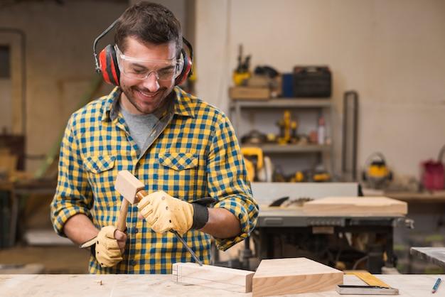 木製のブロックでチゼルを打つ男性の大工を笑顔 無料写真