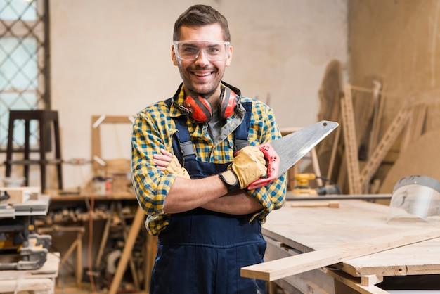 Портрет улыбающегося плотника, держащего ручную пилу, смотрящего на камеру Бесплатные Фотографии