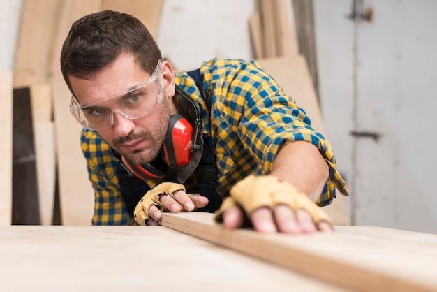 ワークショップの木の表面に板を置く男性の大工 無料写真