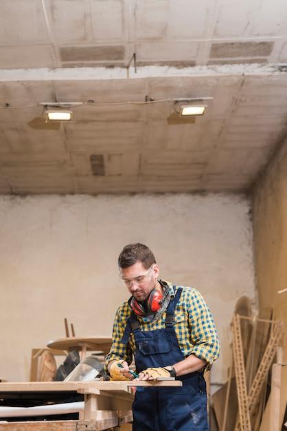 Профессиональный мужской плотник принимая измерения на верстаке в мастерской Бесплатные Фотографии