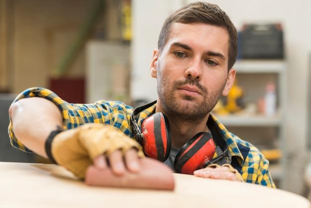 Мужской плотник разглаживает деревянную поверхность на наждачной бумаге Бесплатные Фотографии