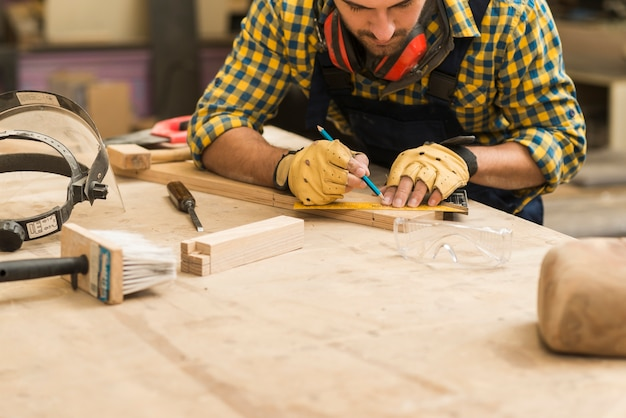 Конец-вверх мужского плотника измеряя деревянный блок с правителем и карандашем на деревянном верстаке Бесплатные Фотографии