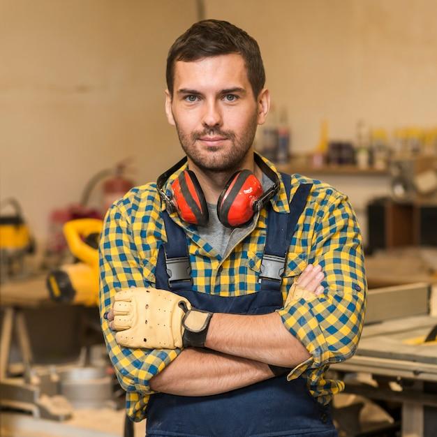 Портрет мужчины-плотника, стоящего со скрещенными руками Бесплатные Фотографии