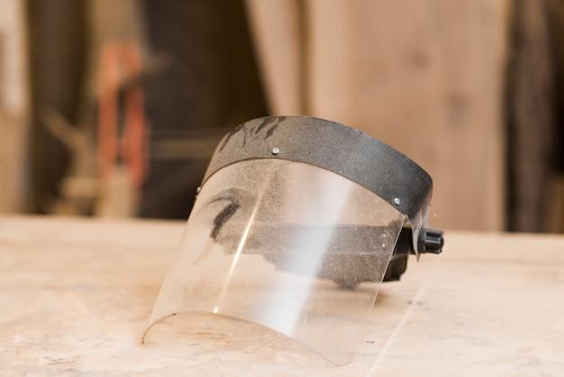 木製テーブル上の透明な顔のマスク 無料写真