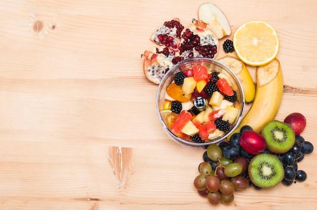 木製のテクスチャの背景に果物とフルーツサラダ 無料写真