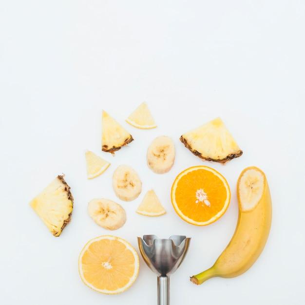 Ломтик ананаса; банан; апельсиновые дольки с электрическим ручным блендером из нержавеющей стали на белом фоне Бесплатные Фотографии