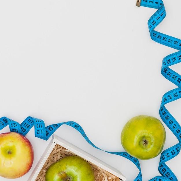 Синий измерительная лента с красными и зелеными яблоками на белом фоне Бесплатные Фотографии