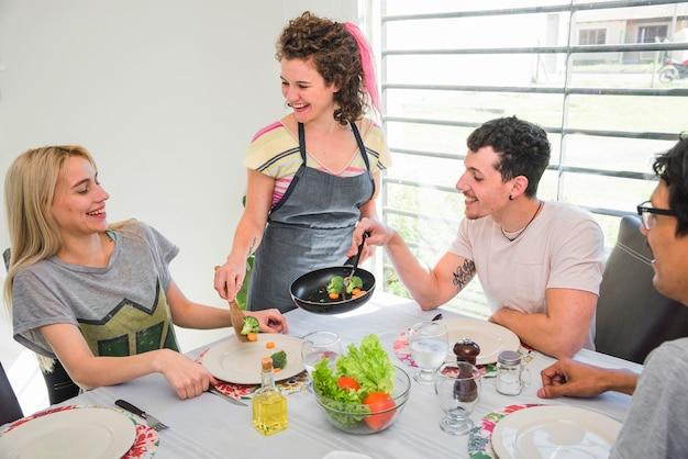ダイニングテーブルで彼女の友人に調理された野菜を提供する笑顔の若い女性 無料写真