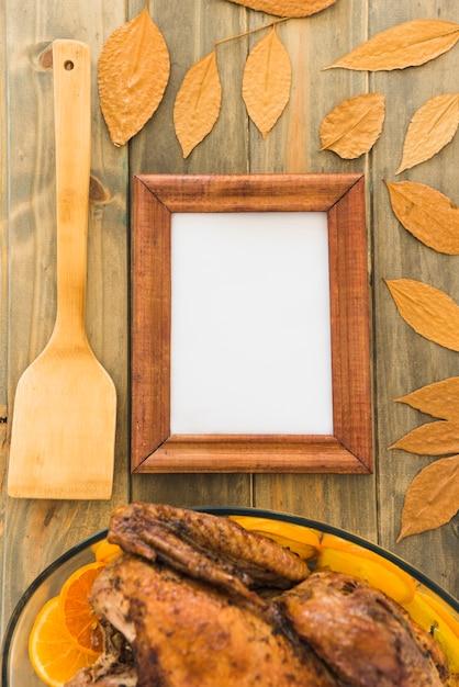 乾いた葉の間のパドルとチキンの近くのフォトフレーム 無料写真