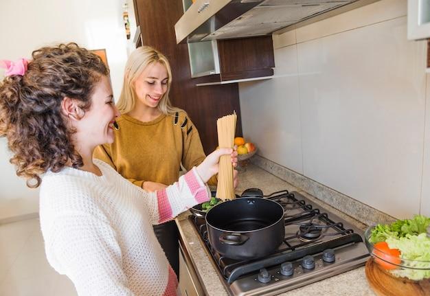 キッチンで彼女の女性の友達とスパゲティを料理する女性 無料写真