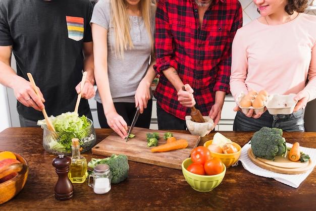 キッチンで食事を準備している友人の中間部分 無料写真