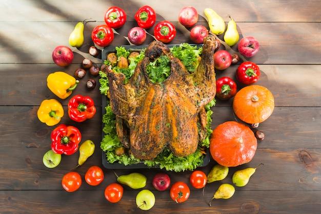 木製のテーブルに野菜と一緒に焼いた七面鳥 無料写真