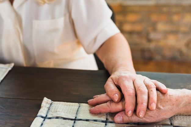 夫の手に触れる高齢の女性 無料写真