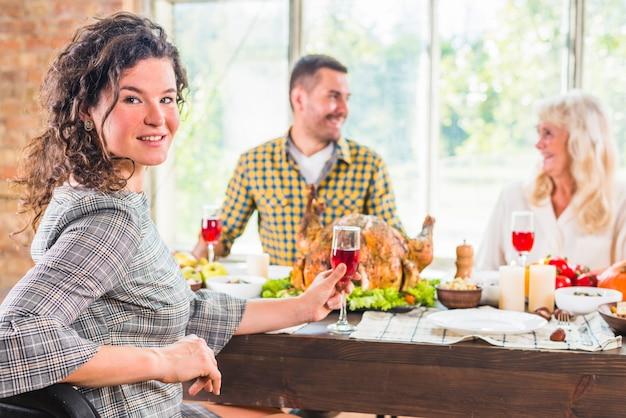 灰色の女性と男性の反対側のテーブルに座っている若い女性 無料写真