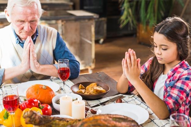 テーブルで祈っている子供と高齢の男 無料写真