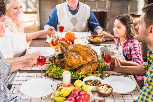 テーブルで手をつないでいる幸せな家族 無料写真