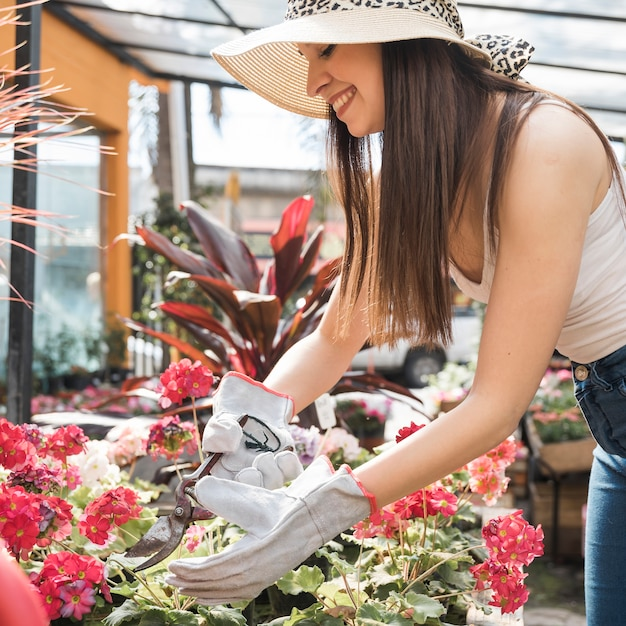 Красивая женщина-садовник срезает цветок ножницами Бесплатные Фотографии