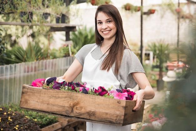 木製の箱にカラフルなペチュニアを保持している笑顔の若い女性の肖像 無料写真