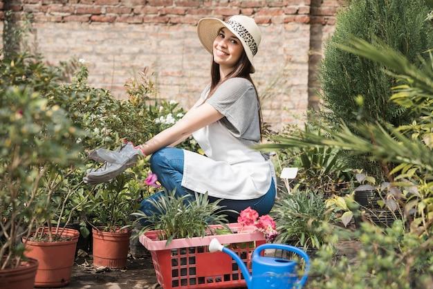 温室で植物を世話している笑顔の若い女性の側面図 無料写真