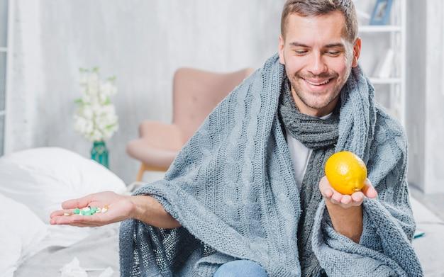 ピルの代わりにレモンを選ぶショールで包んだ笑顔の男 無料写真