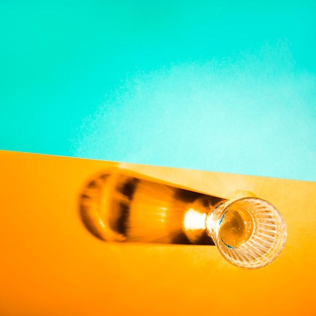 黄色と青緑色の背景に明るい影を持つガラスのオーバーヘッドビュー 無料写真