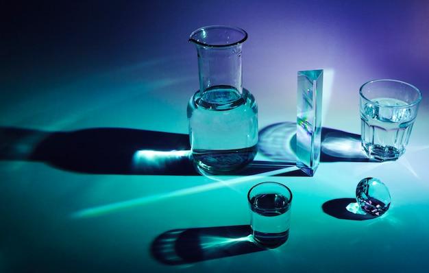 光沢のあるボトル。プリズム;ガラス青色の背景に暗い影とダイヤモンド 無料写真