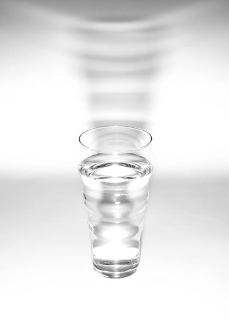 白い背景の上の影付きの水のガラス 無料写真