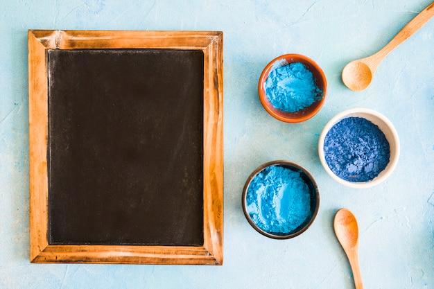 Пустой деревянный сланец с холи цветные чаши и деревянной ложкой на цветном фоне Бесплатные Фотографии