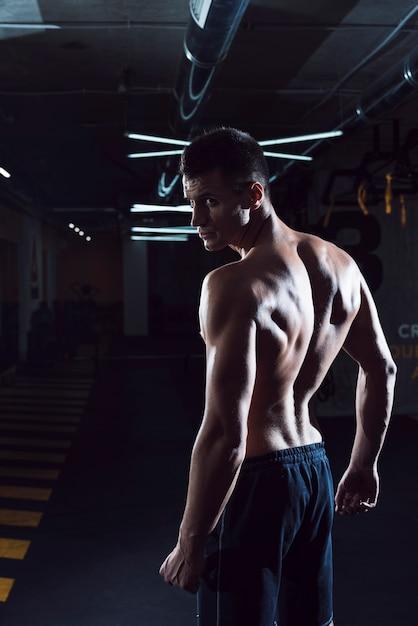 筋肉の若い男がジムに立っている 無料写真