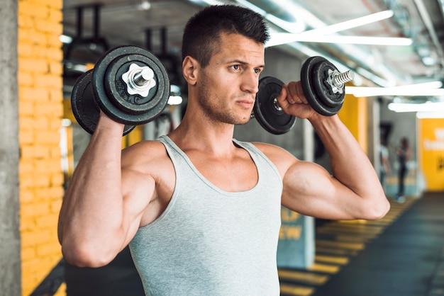 彼の肩を強化するためにダンベルと運動をしている若い男 無料写真