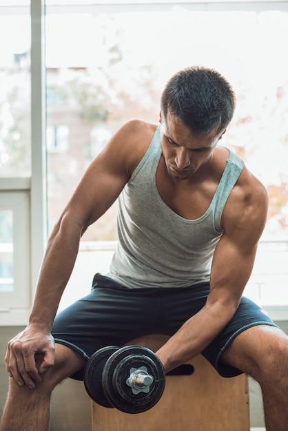 ダンベルでトレーニングをしている筋肉の男 無料写真
