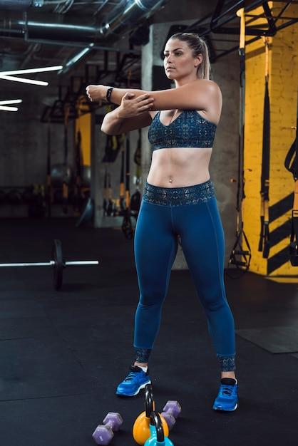 ジムの運動器具の近くで彼女の手を伸ばしている運動の女性 無料写真
