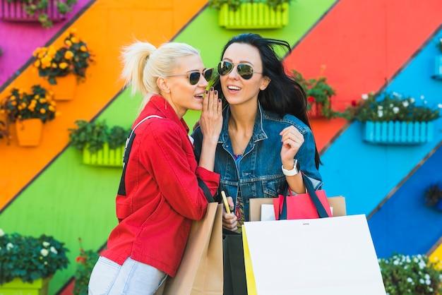 壁の近くで話すバッグを持つ若い女性 無料写真