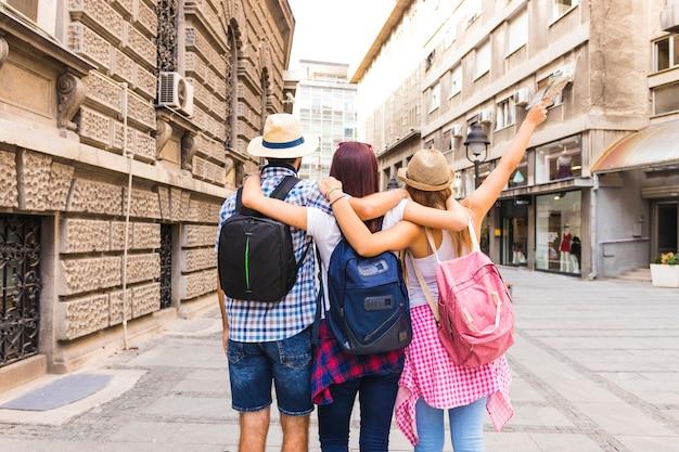 Группа друзей с рюкзаком стоя на улице Бесплатные Фотографии