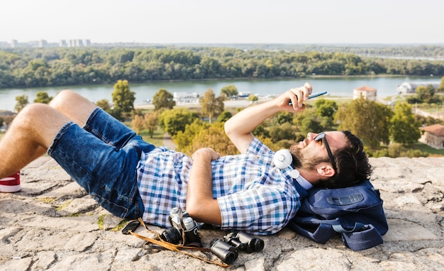携帯電話を使って地面に横たわっている男 無料写真
