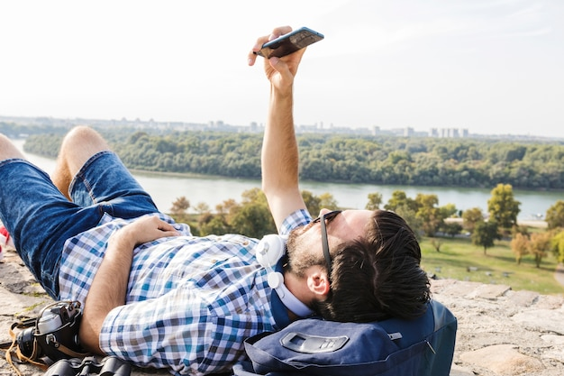 携帯電話を使って地面に横たわっている若い男性のハイカーのクローズアップ 無料写真