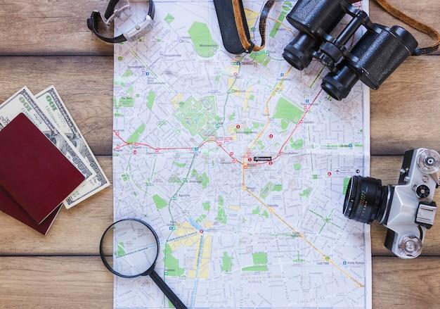 地図;パスポート;紙幣;虫眼鏡;カメラ;双眼鏡と木製の背景に腕時計 無料写真