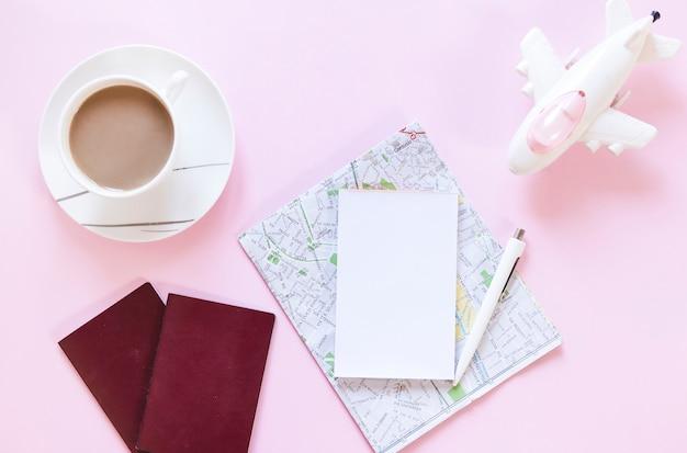 Чашка чая; паспорт; карта; бумага; ручка и самолет на розовом фоне Бесплатные Фотографии