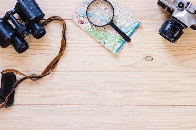 Повышенный вид на бинокль; увеличительное стекло; карта и камера на деревянной поверхности Бесплатные Фотографии