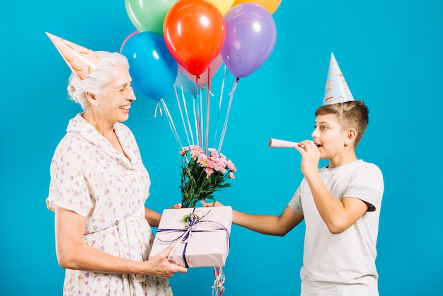 幸せな年配の女性、誕生日の贈り物と花を見て彼女の孫を吹くパーティーホーン 無料写真