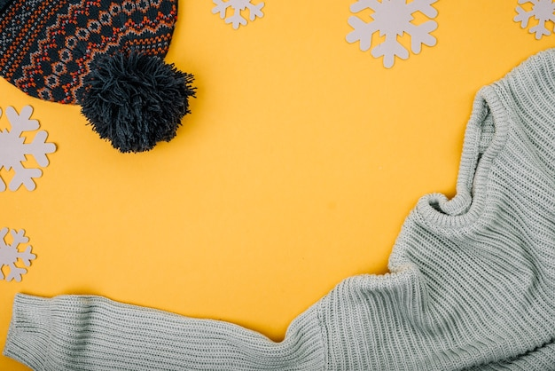 スノーフレークの近くのセーターとボブルの帽子 無料写真