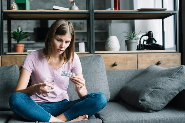 水と薬のガラスでソファに座って病気の女 無料写真