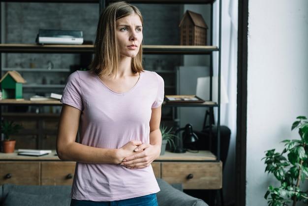 胃の痛みを患っている若い女性 無料写真